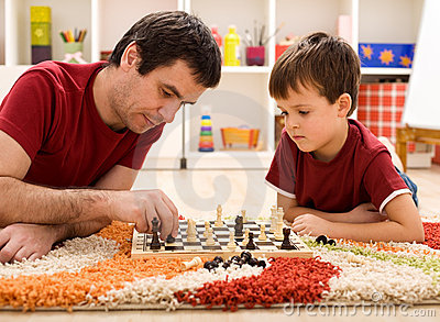 Father teaching son the rules of chess