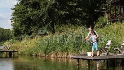 Father teaching son to fish at freshwater pond stock footage