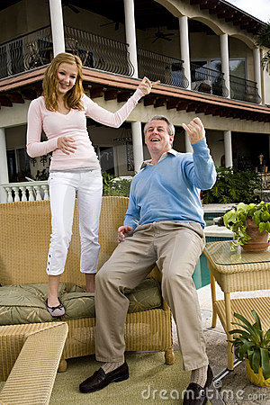 Father and teen daughter playing air guitar