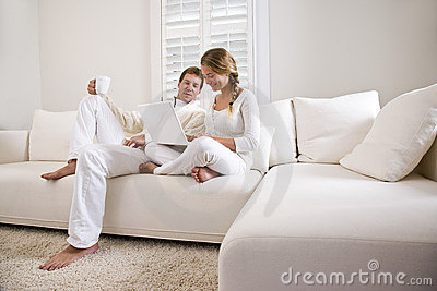 Father and teen daughter on white sofa with laptop