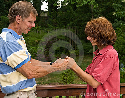 Father and teen son fist-bumping