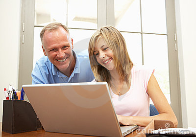 Father And Teenage Daughter Using Laptop At Home