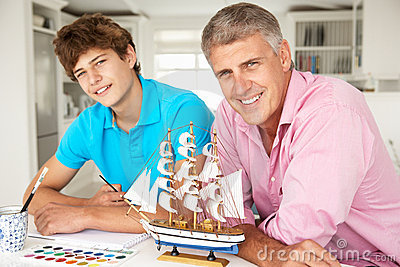 Father and teenage son model making