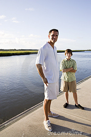 Father and teenage son standing on dock by water