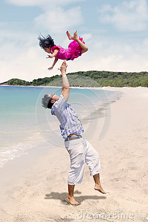 Father throw daughter in the air at beach
