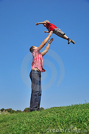 Father throwing his son in the air and catching hi
