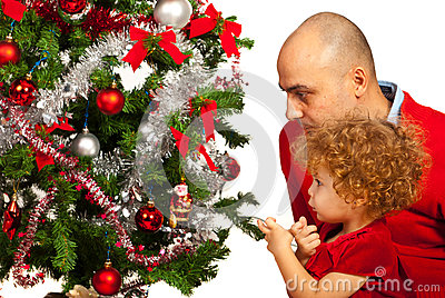 Father and toddler girl decorate tree