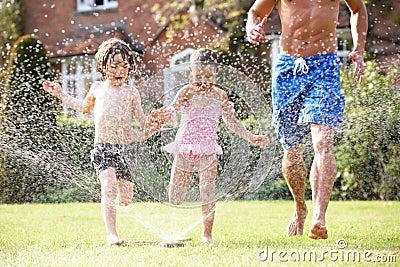 Father And Two Children Running Through Garden