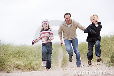 Father and two young children running at beach