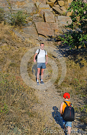 Father waiting for his small son while hiking
