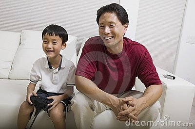 Father watching son play video game on couch