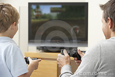Father And Young Son Playing With Game Console