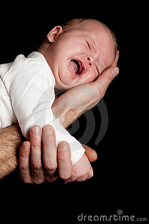 A fathers hand is holding a crying newborn baby
