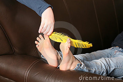 Feather tickling bare feet