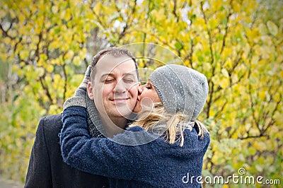 Fecha. La mujer joven besa a un hombre sonriente.
