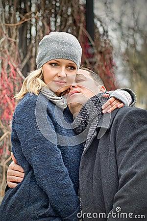 Fecha. La mujer rubia joven abraza a un hombre al aire libre