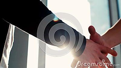 Fechamento de dois homens de negócios apertados de mão no fundo do sol