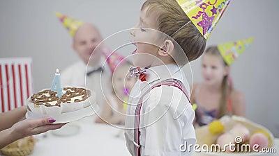 Fechamento de garotinho caucasiano soprando vela na figura 4 do bolo de aniversário Jovens que festejam comemorando vídeos de arquivo