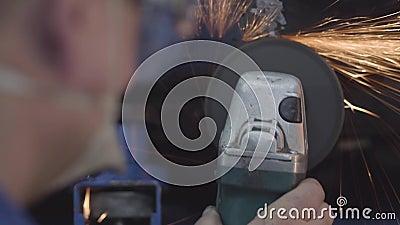 Fechamento de um homem cacasiano não reconhecível usando triturador de metal Mecânico automóvel profissional a trabalhar na ofici vídeos de arquivo