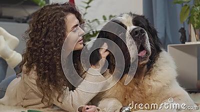 Fechamento de uma mulher caucasiana morena tocando a orelha de Saint Bernard e falando Garota sorridente descansando com bicho de vídeos de arquivo