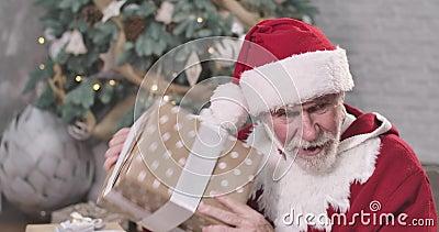 Fechamento do Pai Natal idoso sentado no fundo da árvore de Natal e caixa de presentes agitada Velho curioso tentando video estoque