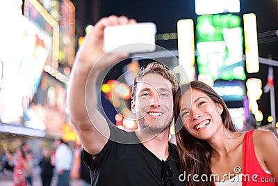 Fechando los pares jovenes felices en el amor que toma la foto del selfie en Times Square, New York City en la noche. Turista mult