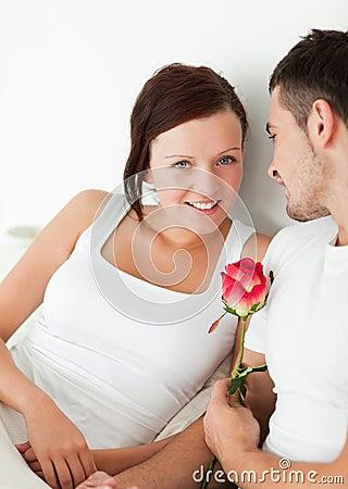 Feche acima de um par alegre com uma rosa