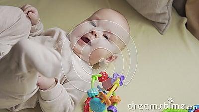 Feche acima do beb? que luying na cama e que sorri na c?mera Conceito da inf?ncia vídeos de arquivo
