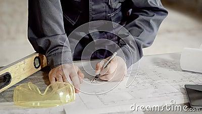 Feche acima do tiro nas mãos do ` s do homem, que faz anotações no desenho de construção para o contramestre e os construtores, o vídeos de arquivo