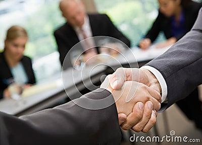 Feche acima dos homens de negócios que agitam as mãos