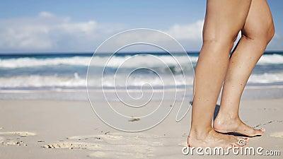 Feche acima dos pés da mulher que andam na praia filme