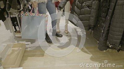 Feche acima dos pés da mulher que vestem um equipamento ocasional que anda e que procura a roupa com os sacos de compras em suas  filme