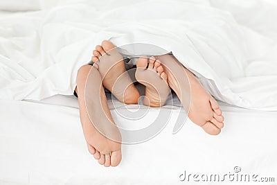 Feche acima dos pés do par em sua cama