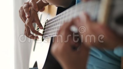 Feche as mãos macabras de uma mãe ensinando a uma filha a tocar violão clássico acústico, atividade familiar para autoaprendizage video estoque
