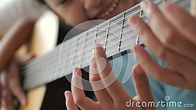 Feche as mãos macabras de uma mãe ensinando a uma filha a tocar violão clássico acústico, atividade familiar para autoaprendizage filme