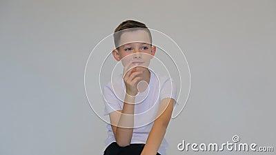 Feche o garoto pensante sobre fundo cinza Conceito de expressão duvidosa filme