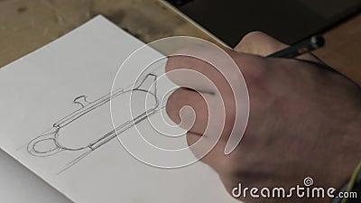 Fecho de uma mão masculina desenhando um esboço de bule de barro no papel Mão masculina desenha com lápis Exibição de macro vídeo vídeos de arquivo