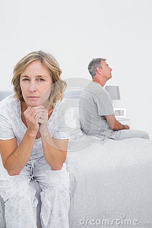 Fed up couple sitting on different sides of bed having a dispute