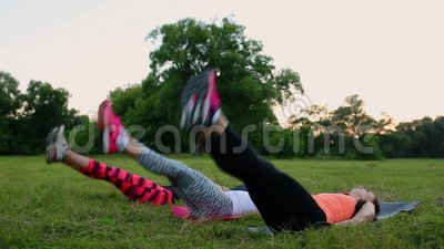 Feeling your abs girls. Group of young athletic people in sportswear doing physical exercises on green grass in summer. Park outdoors, side view stock video footage