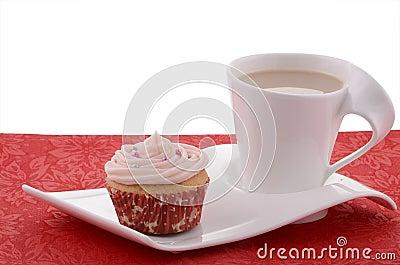Feestelijke cupcake met thee op buitensporige plaat