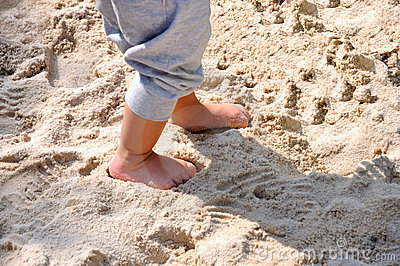 Feet of a child on sand