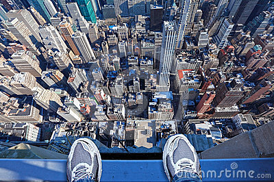 Feet on the edge of tall building