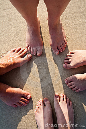 Feet of a family in the fine sand of the beach