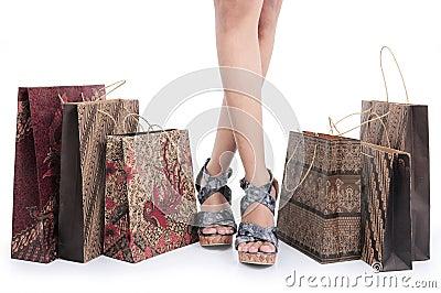Feet of a girl and batik shopping bags