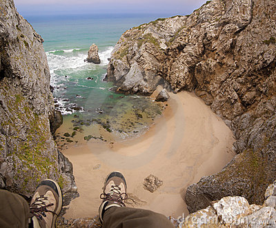 Feet hanging over beach cliff