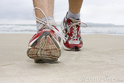 Feet of man jogging on a beach
