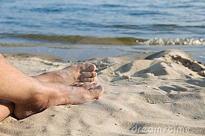 The feet of man lie on sand