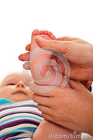 Feet massage of infant girl
