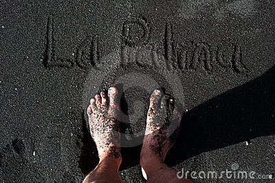 Feet standing on a black sand beach of La Palma