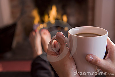 Feet warming at a fireplace with coffee